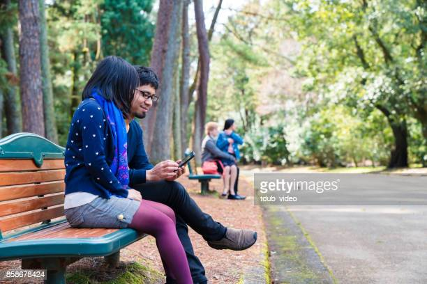 japanese young couple sitting a bench outside using a phone - tdub_video stock pictures, royalty-free photos & images