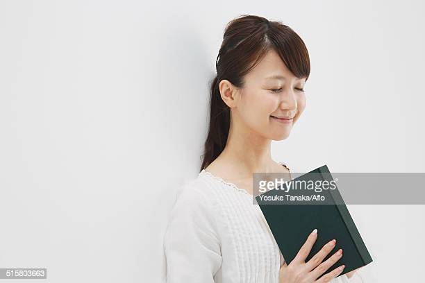 Japanese young woman in a white shirt with a book against white background