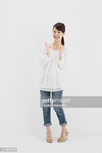 japanese young woman in jeans and white shirt standing against white background - 拍手喝采 ストックフォトと画像