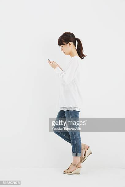 japanese young woman in jeans and white shirt with smartphone standing against white background - 白いシャツ 女性 ストックフォトと画像