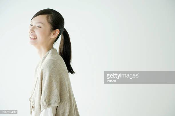 japanese young woman laughing, side view - 黒髪 ストックフォトと画像
