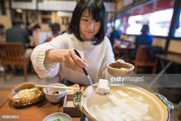 Japanese young woman picking up tofu from hot pot