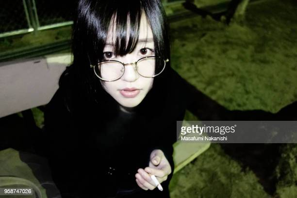 Japanese young woman smoke a cigarette at night