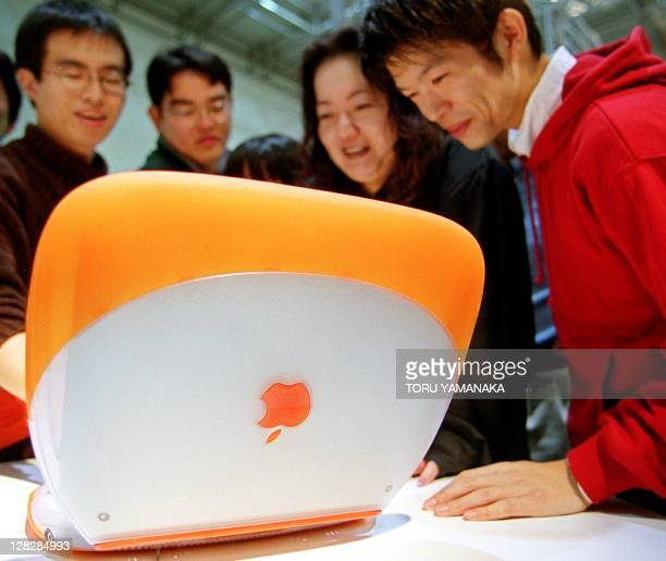 Japanese youths smile as they look at the new iBook from US computer maker Apple Computer Inc at a department store in Tokyo 16 October 1999 The firm...