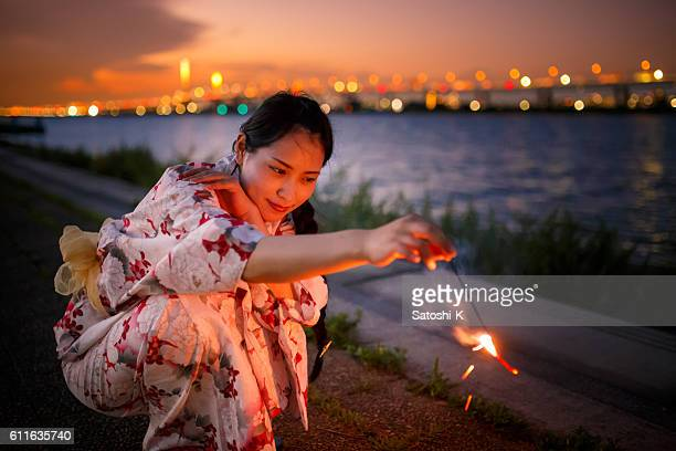 Japanese yukata woman playing with sparklers in twilight