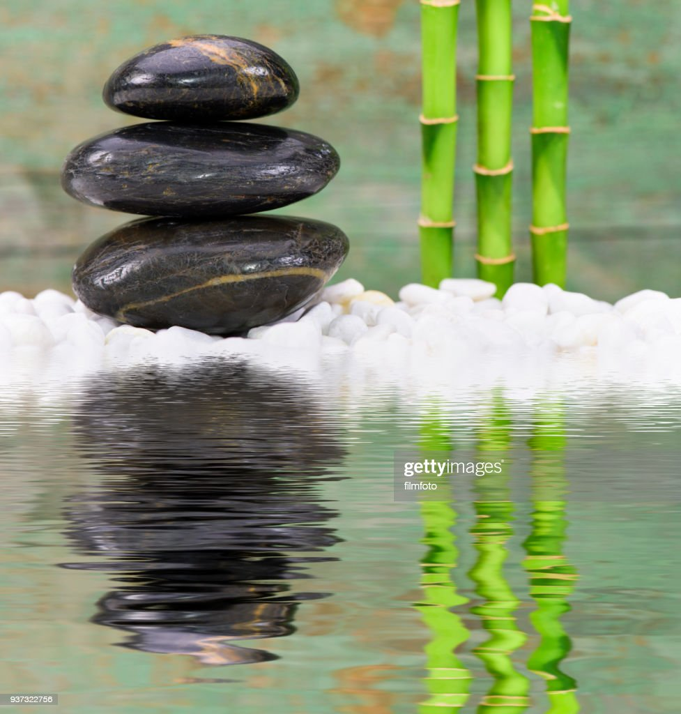Japanese Zen Garden With Stacked Stones Mirroring In Water