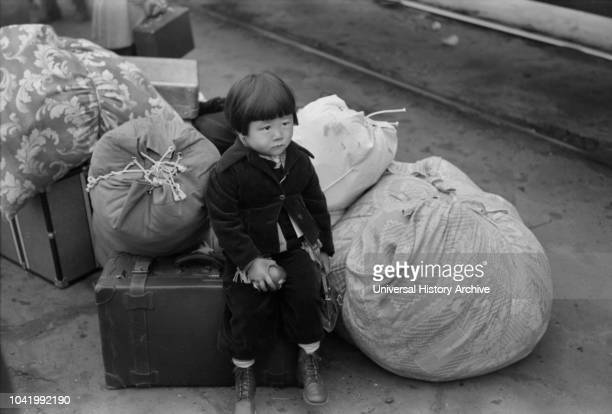 Japanese-American Child Waiting for Train to Owens Valley During Evacuation of Japanese-Americans from West Coast Areas under US Army War Emergency...