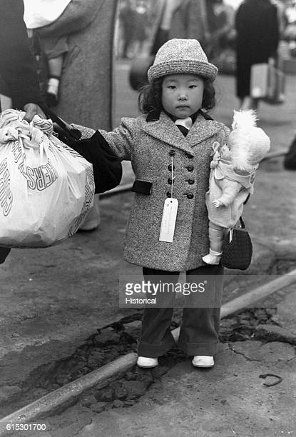 JapaneseAmerican child waiting in Los Angeles California to go with his parents to Owens Valley JapaneseAmericans were evacuated from certain West...