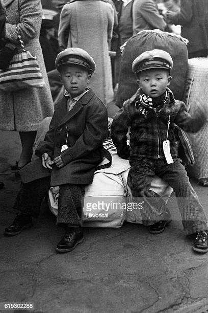 JapaneseAmerican children waiting with their luggage at the old Santa Fe station in Los Angeles California for a train to take them to Owens Valley...