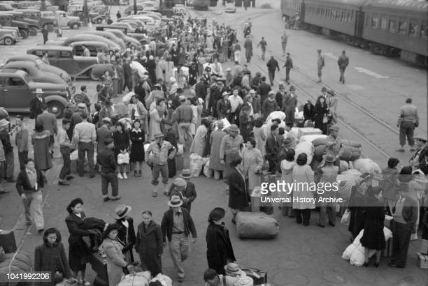 JapaneseAmericans Waiting for Train to Owens Valley During Evacuation of JapaneseAmericans from West Coast Areas under US Army War Emergency Order...
