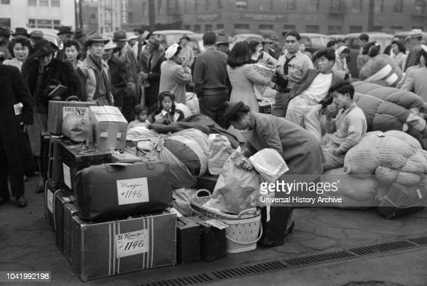 JapaneseAmericans with Baggage Waiting for Train to Owens Valley During Evacuation of JapaneseAmericans from West Coast Areas under US Army War...