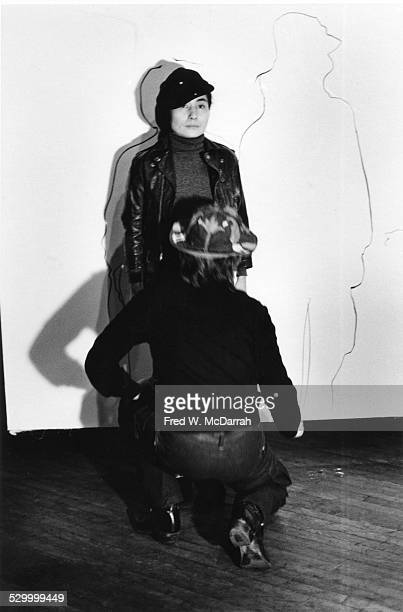 Japaneseborn American artist and musician Yoko Ono traces the body of her husband British musician John Lennon as part of a performance art piece at...