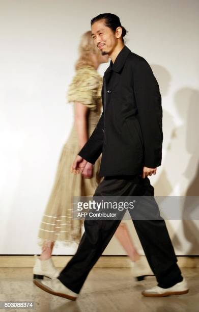 Japaneseborn Australian designer Akira Isogawa receives applause at the end of his parade which opened Australian Fashion Week in Sydney 05 May 2003...