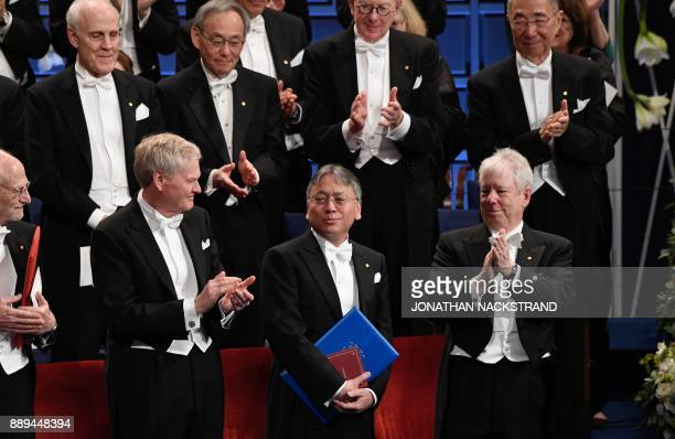 Japaneseborn British novelist Kazuo Ishiguro is applauded by US geneticist and Nobel Prize in Physiology or Medicine 2017 laureate Michael W Young...