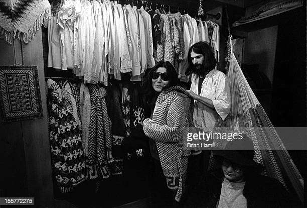 Japaneseborn musician and artist Yoko Ono tries on a coat in a unidentified shop in the neighborhood around Bank Street in Greenwich village as her...