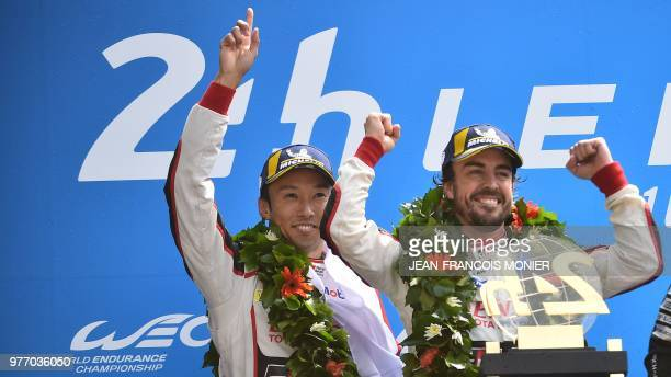 Japanese's Kazuki Nakajima and Spain's driver Fernando Alonso celebrate on the podium after winning the 86th Le Mans 24hours endurance race at the...