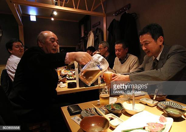 JapanlifestylefooddrinkeconomyFOCUS by Daniel LEUSSINK This picture taken on December 28 2015 shows people drinking beer at a yearend party at a pub...