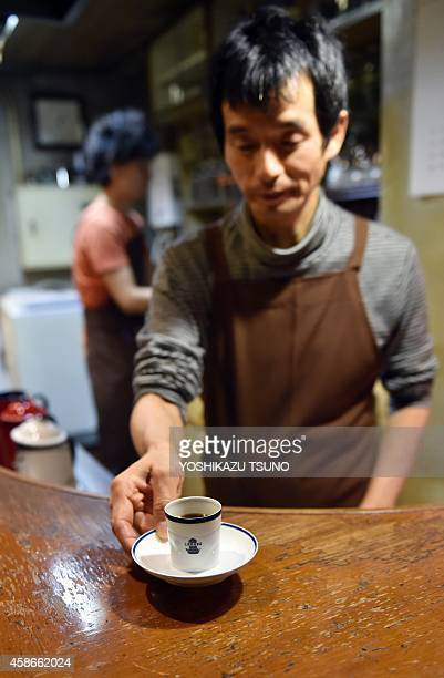 JapanlifestyleleisurecoffeeFEATURE This picture taken on October 8 2014 shows a barista of a coffee shop Cafe de L'Ambre serving a cup of coffee at...