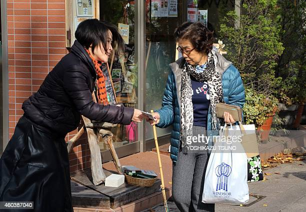 JapanpoliticsvotewomenFOCUS This picture taken on December 12 2014 shows Mizuho Nakayama a member of the 'Ikereru Joshikai' gives a flyer of an...