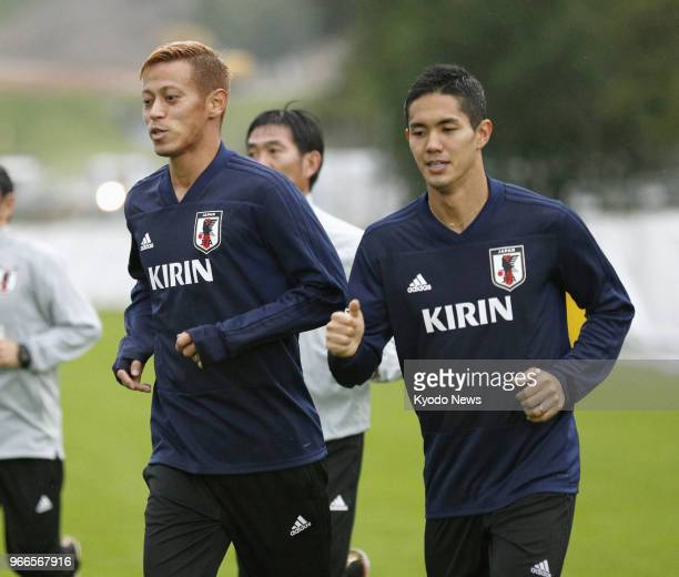 Japan's 23man squad members Keisuke Honda and Yoshinori Muto jog during a training session on the outskirts of western Austria city Innsbruck on June...