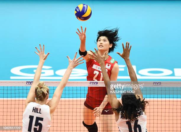 TOPSHOT Japan's Ai Kurogo pushes the ball over US Kimberly Hill and Foluke Akinradewo during the 2018 FIVB World Championship volleyball women's...