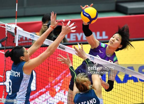 Japan's Aika Akutagawa spikes the ball over Argentina's Julieta Lazcano and Paula Nizetich during the FIVB Women's World Cup volleyball match between...