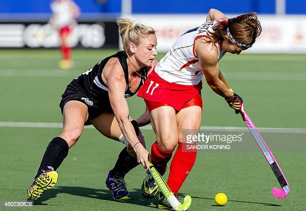 Japan's Akane Shibata fights for the ball with New Zealand's Stacey Michelsen during a stage match in the women's tournament of the Field Hockey...