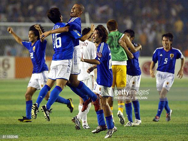 Japan's Alex celebrates with Toshiya Fujita and teammates at the end of their Asian Cup soccer final win over China 07 August 2004 in Beijing's...
