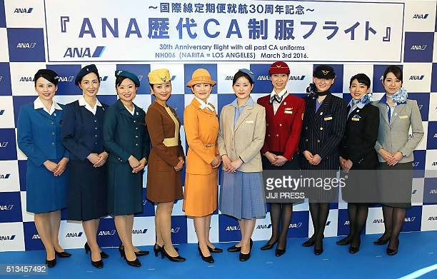 Japan's All Nippon Airways flight attendants who wear successive 10 uniforms since 1955 pose for photographers during a ceremony before they board a...