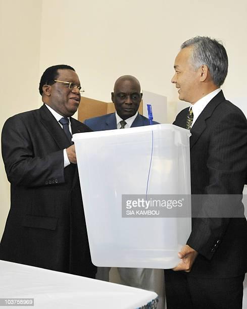 Japan's ambassador to Ivory Coast Okmura Yoshifumi gives a ballot box to Youssouf Bakayoko president of the Ivory Coast's Independent Electoral...