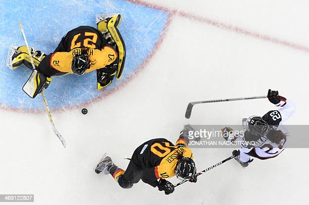 Japan's Ami Nakamura vies with Germany's goalkeeper Viona Harrer and Germany's Anja Weisser during the Women's Ice Hockey Group B match Japan vs...