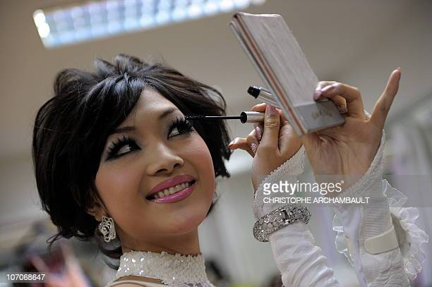 Japan's Ami Takeuchi applies makeup backstage ahead of the Miss International Queen 2010 beauty pageant in southeastern Thailand's city of Pattaya...