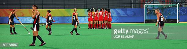 Japan's and US players walk on the pitch during their women's field hockey match against Japan of the 2008 Beijing Olympic Games at the Olympic Green...
