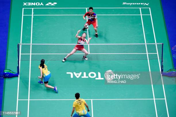 Japan's Arisa Higashino and Yuta Watanabe hit a return against Thailand's Savitree Amitrapai and Dechapol Puavaranukroh during their mixed doubles...