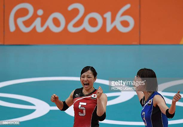 Japan's Arisa Sato and Japan's Saori Kimura celebrate winning a point during the women's qualifying volleyball match between Japan and South Korea at...