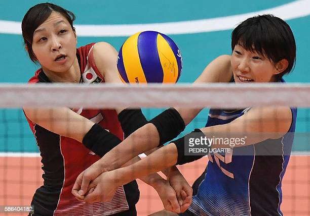 Japan's Arisa Sato and Japan's Yuki Ishii clash as they vie to set the ball during the women's qualifying volleyball match between Japan and South...