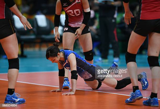 Japan's Arisa Sato takes a fall during the women's qualifying volleyball match between Brazil and Japan at the Maracanazinho stadium in Rio de...