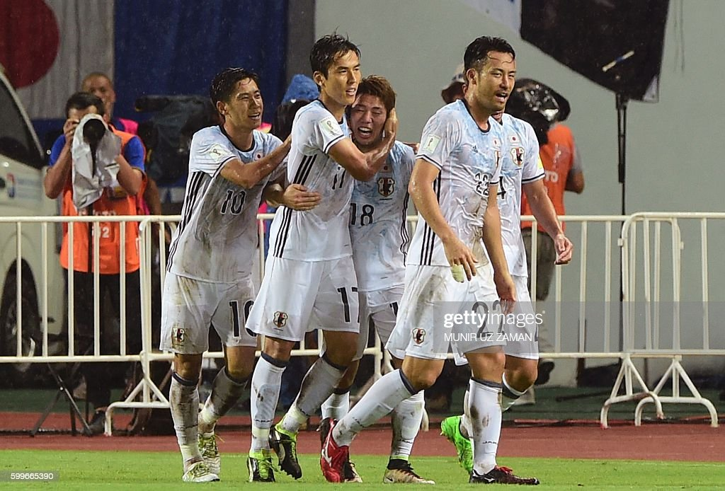 Japan's Asano Takuma (3rd L) celebrates with his teammates after scoring a goal during the 2018 World Cup football qualifying match between Thailand and Japan in Bangkok on September 6, 2016. / AFP / Munir UZ