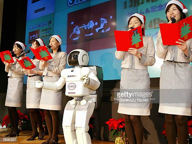 Japan's auto giant Honda Motor showroom female employees sing Christmas songs while Honda's humanoid robot Asimo conducts them at the company's...