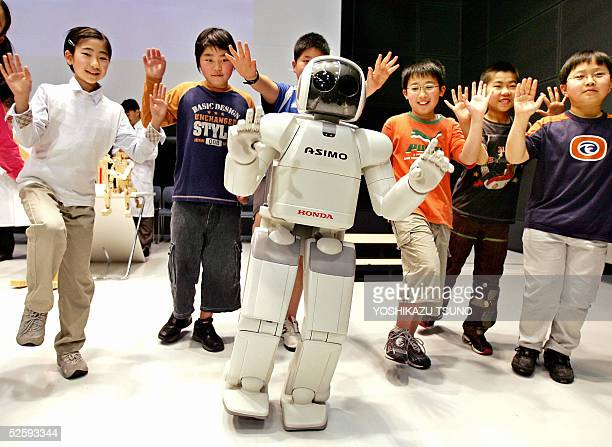 Japan's auto giant Honda Motor's humanoid robot Asimo balances on one leg along with elementary school children during a press preview in Tokyo 06...