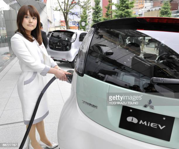 Japan's auto giant Mitsubishi Motors employee charges the company's first mass production electric vehicle 'iMiEV' at the company's headquarters in...
