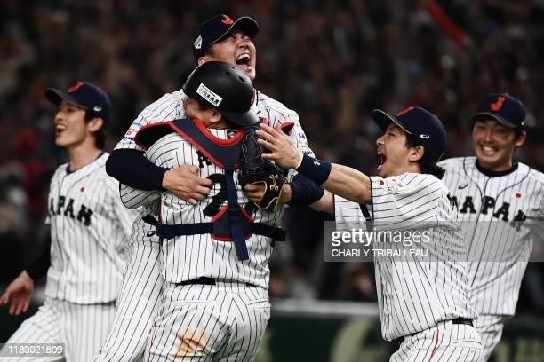Japan's baseball players Yasuaki Yamasaki and Tsubasa Aizawa celebrate with teammates their win against South Korea after the WBSC Premier 12 Super...