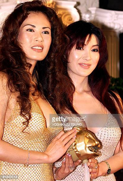Japan's buxom beauties Kyoko Kano and Mika Kano known as 'Kano sisters' shows off a golden faucet in the shape of a lion's head called 'Cleopatra's...