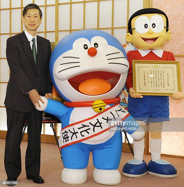 Japan's cartoon character Doraemon who has been appointed as the nation's first Anime Ambassador poses with Foreign Minister Masahiko Komura and...