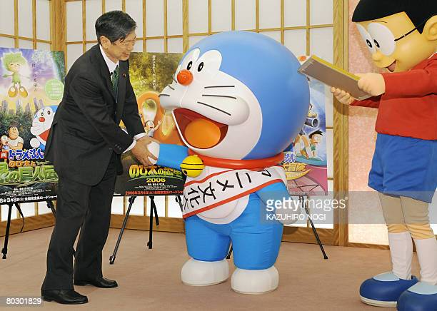 Japan's cartoon character Doraemon who has been appointed as the nation's first Anime Ambassador is congratulated by Foreign Minister Masahiko Komura...