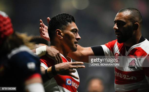 Japan's centre Timothy Lafaele celebrates with teammates including Japan's lock and captain Michael Leitch after scoring a try during the friendly...