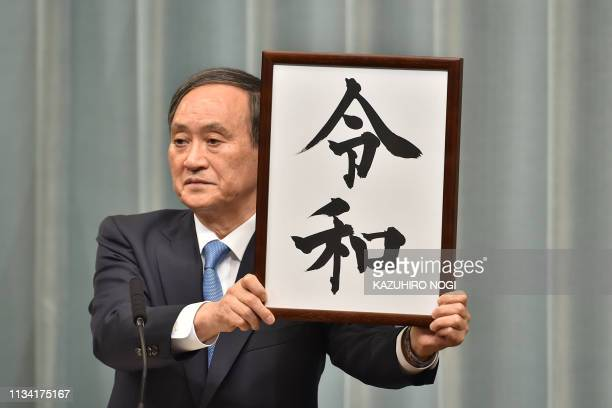 Japans Chief Cabinet Secretary Yoshihide Suga holds the new era name Reiwa during a press conference at the prime ministers office in Tokyo on April...