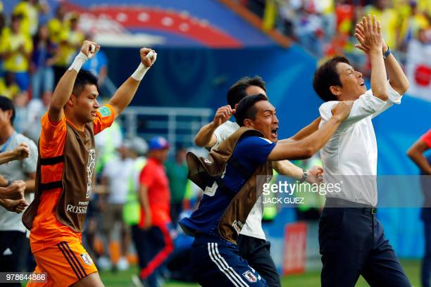 Japan's coach Akira Nishino celebrates with players at the end of the Russia 2018 World Cup Group H football match between Colombia and Japan at the...