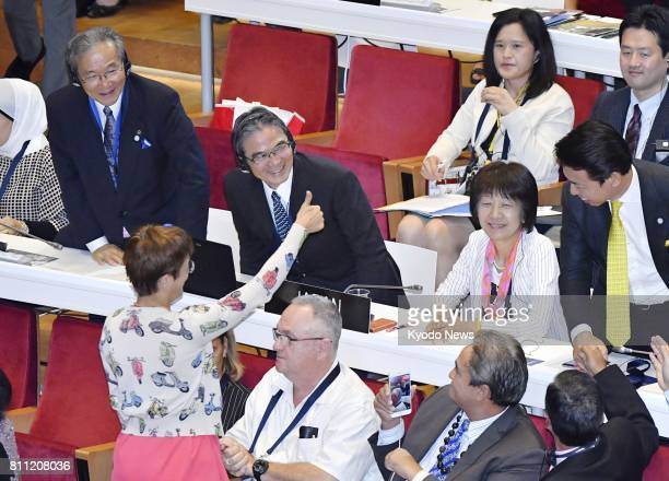 Japan's Commissioner for Cultural Affairs Ryohei Miyata and other Japanese officials celebrate during a session of the World Heritage Committee of...