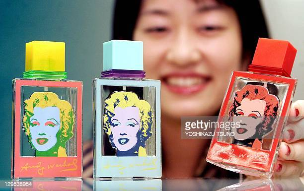 Japan's cosmetics maker Kanebo employee Seiko Kuwahata displays bottles of eau de toilette designed with Andy Warhol's Marilyn Monroe at the...